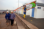 Two elderly ladies walk along to a younger man carrying a windsurfing sail on the seafront at the Devon resort of Paignton. A small pet dog is being exercised on a lead on an overcast day and beach huts stretch into the distance towards the town centre. The male in a wet suit has the sail resting on his head but the women don't seem to notice.