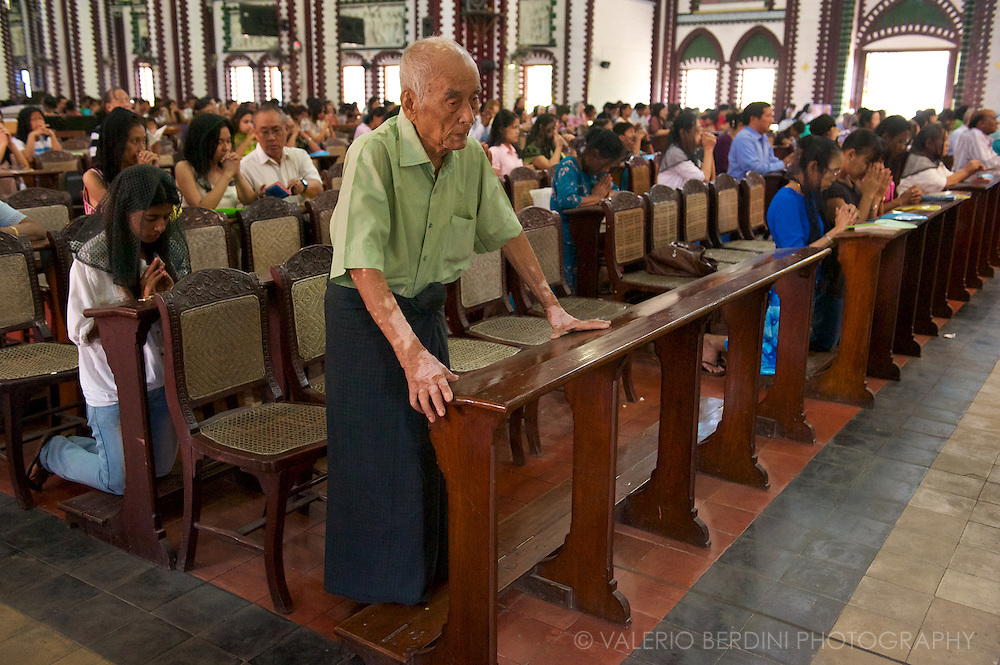 An old Burmese man, part of the small catholic community, prays on Easter day in Rangoon Saint Mary's Cathedral.