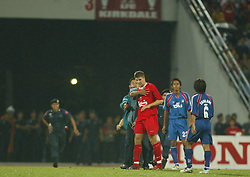 BANGKOK, THAILAND - Thailand. Thursday, July 24, 2003: A Thai fan runs onto the pitch to shake hands with Steven Gerrard, chased by security, during a preseason friendly match at the Rajamangala National Stadium. (Pic by David Rawcliffe/Propaganda)
