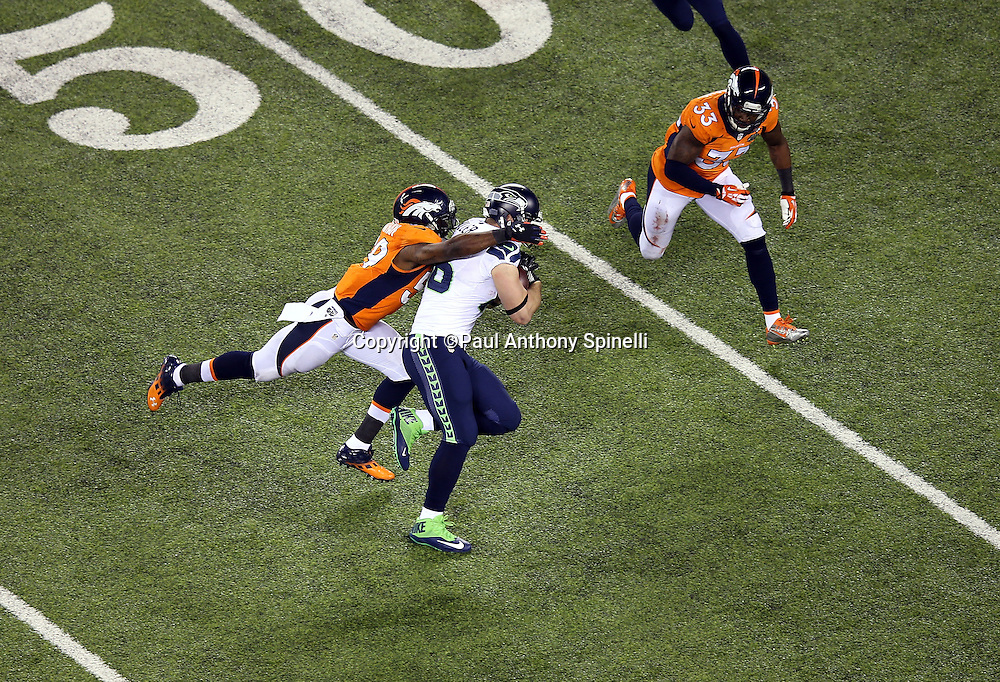 Seattle Seahawks tight end Zach Miller (86) tries to elude a tackle attempt by Denver Broncos outside linebacker Danny Trevathan (59) after catching a fourth quarter pass during the NFL Super Bowl XLVIII football game against the Denver Broncos on Sunday, Feb. 2, 2014 in East Rutherford, N.J. The Seahawks won the game 43-8. ©Paul Anthony Spinelli