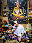 "25 MAY 2015 - BANGKOK, THAILAND:  AJARN NENG ONNUT (also known as Khun Pean) in his Sak Yant tattoo parlor. Sak Yant (Thai for ""tattoos of mystical drawings"" sak=tattoo, yantra=mystical drawing) tattoos are popular throughout Thailand, Cambodia, Laos and Myanmar. The tattoos are believed to impart magical powers to the people who have them. People get the tattoos to address specific needs. For example, a business person would get a tattoo to make his business successful, and a soldier would get a tattoo to help him in battle. The tattoos are blessed by monks or people who have magical powers. Ajarn Neng, a revered tattoo master in Bangkok, uses stainless steel needles to tattoo, other tattoo masters use bamboo needles. The tattoos are growing in popularity with tourists, but Thai religious leaders try to discourage tattoo masters from giving tourists tattoos for ornamental reasons.       PHOTO BY JACK KURTZ"