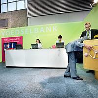 """Nederland, Amsterdam , 9 januari 2012..Op de Horecava, """"de"""" Horecabeurs van Nederland in de RAI staat een stand van de voedselbeurs..Op de foto stopt een aandeelhouder van de voedselbank zijn aandeel in de kluis..Vervolgens zal het aandeel door medewerkers van de stand eruit gehaald worden en het aandeel kan men vervolgens bekijken online..Links bekijkt 1 van de standhouders van de voedselbank de aandelen van Nederlandse aandeelhouders vd voedselbank op een scherm..Foto:Jean-Pierre Jans"""