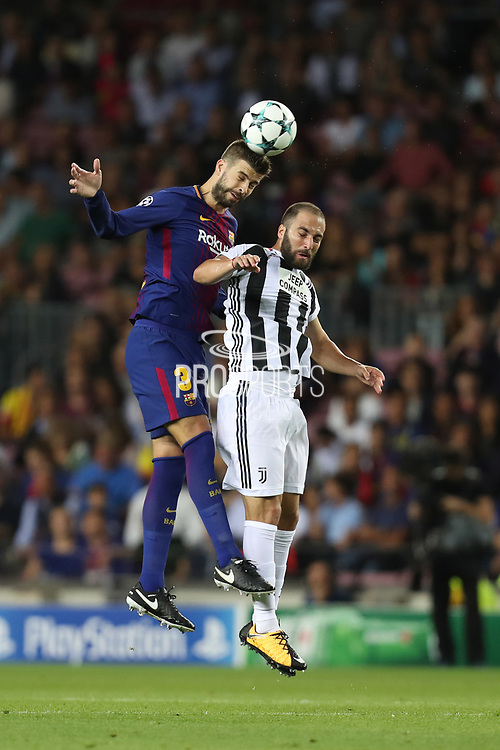Gerard Pique of FC Barcelona heads the ball under pressure from Gonzalo Higuain of Juventus during the UEFA Champions League, Group D football match between FC Barcelona and Juventus FC on September 12, 2017 at Camp Nou stadium in Barcelona, Spain. Photo: Manuel Blondeau/AOP.Press/ProSportsImages / DPPI
