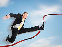 Business man jumping through red tape digital composite