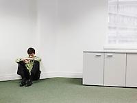 Businessman sitting on floor in corner of office