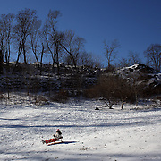 A young girl sledding in Central Park after New York City was hit with over 7 inches of snow during its first winter storm of the year. Central Park, Manhattan, New York, USA. 4th January 2014 Photo Tim Clayton