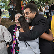 CHARLOTTESVILLE,VA-AUG12: Cornell West hugs counter protestors outside Emancipation Park during the Unite the Right Rally, while the self-proclaimed group, The Militia, stands guard. (Photo by Evelyn Hockstein/For The Washington Post)