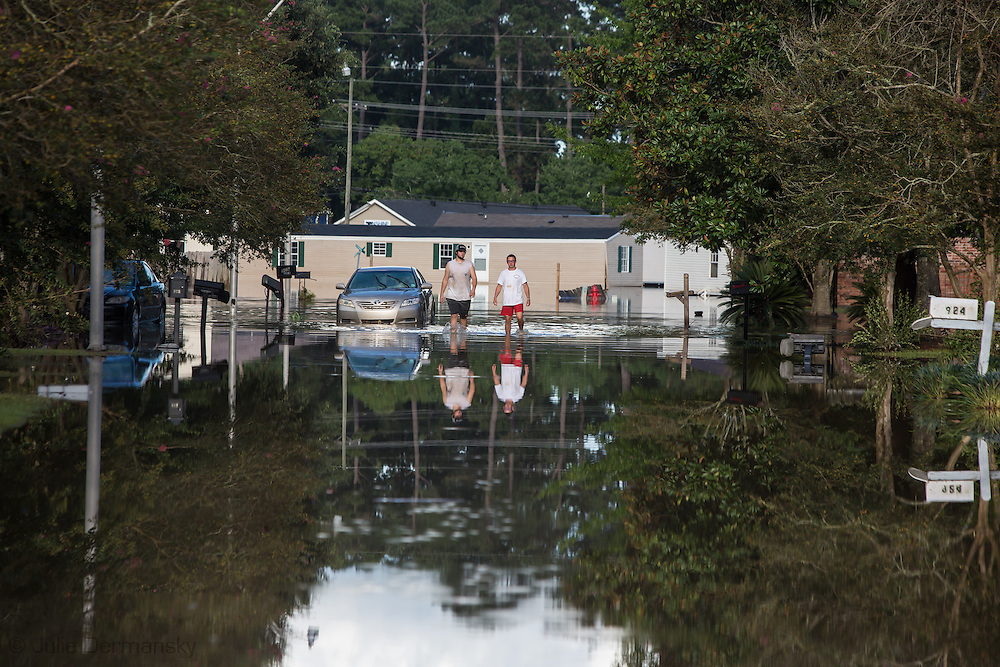 Aug 15, , Cameron DeBate  and his cousin,Forrest Bellue, walk through his flooded neighborhood in Denham Springs Louisiana near his home, on the first day they could return to the area.