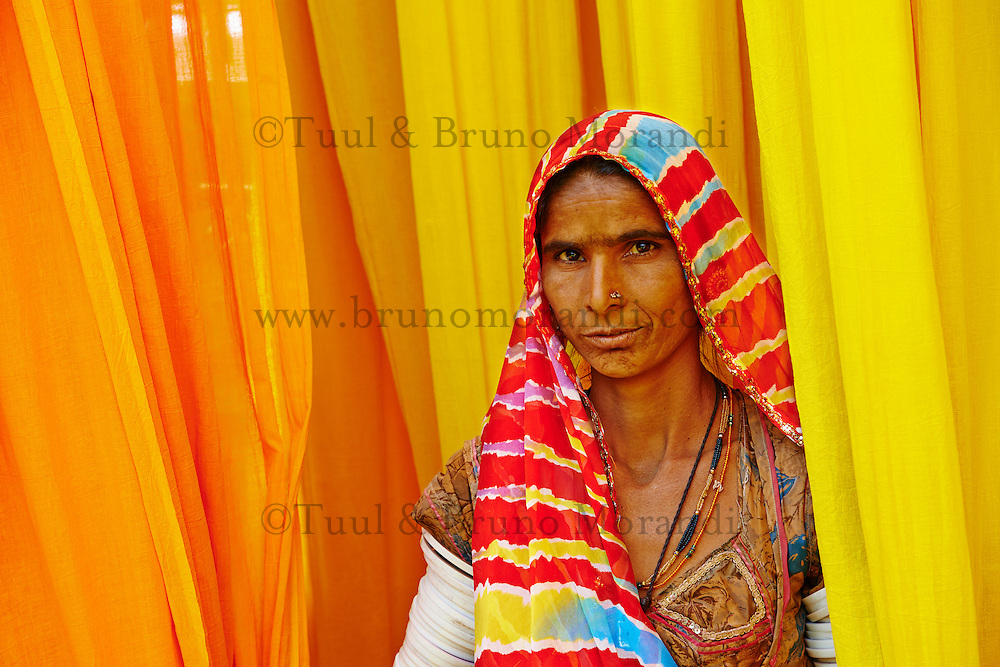 Inde, Rajasthan, Usine de Sari, Lesmay, 40 ans. Les tissus sechent en plein air. Ramassage des tissus secs par des femmes et des enfants avant le repassage. Les tissus pendent sur des barres de bambou. Les rouleaux de tissus mesurent environ 800 m de long. . // India, Rajasthan, Sari Factory, Lesmay, 40 old. Textile are dried in the open air. Collecting of dry textile  are folded by women and children. The textiles are hung to dry on bamboo rods. The long bands of textiles are about 800 metre in length.