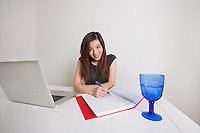 Portrait of confident young businesswoman writing on diary at office desk