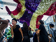 22 OCTOBER 2017 - BANGKOK, THAILAND: People walk under and photograph a Thai flag made from flowers in front of Pak Khlong Talat, the flower market, in Bangkok. There is a replica crematorium south of the flower market and the street in front features elaborate displays in the late king's honor. The King died in October 2016 and will be cremated on 26 October 2017.     PHOTO BY JACK KURTZ
