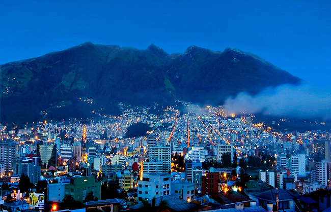 The blue light of dawn illuminates the Andes Pichincha Volcano and passing clouds, in the second highest capital city of the world, Quito, Ecuador.