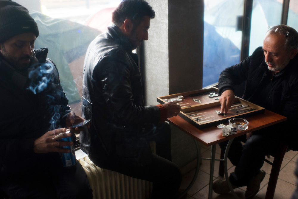 Refugees play backgammon in a cafe at a train station adjacent to a refugee camp on the Macedonian (FYROM) border on March 9, 2016 in Idomeni, Greece.