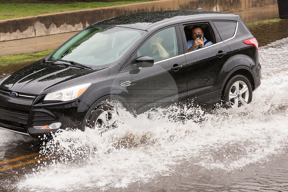 A tourist snaps a photo out the window of their car as they pass through floodwater along the Battery in the historic district as Hurricane Joaquin brings heavy rain, flooding and strong winds as it passes offshore October 4, 2015 in Charleston, South Carolina.