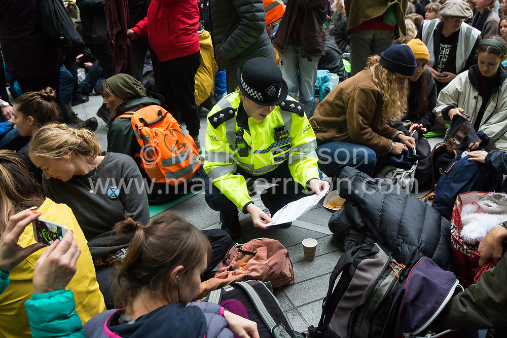 London, UK. 11 October, 2019. Police officers issue warnings under Section 14 of the Public Order Act 1986 to climate activists from Extinction Rebellion blocking the main entrance to the BBC's New Broadcasting House on the fifth day of International Rebellion protests. The activists were demanding that the broadcaster 'tell the truth' regarding the climate emergency.