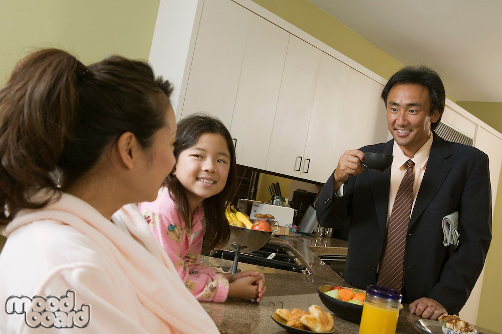 Family at breakfast table father ready for work