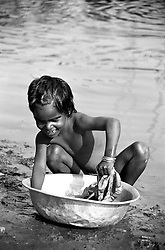 BANGLADESH DHAKA JUL94 - A young girl washes some clothing in a bowl on the shore of the Buriganga River near Dhaka...The Bangladesh Bureau of Statistics estimates the total working child population between 5 and 17 years old to be at 7.9 million...jre/Photo by Jiri Rezac..© Jiri Rezac 1994
