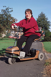 Woman with disability riding electric scooter across park,