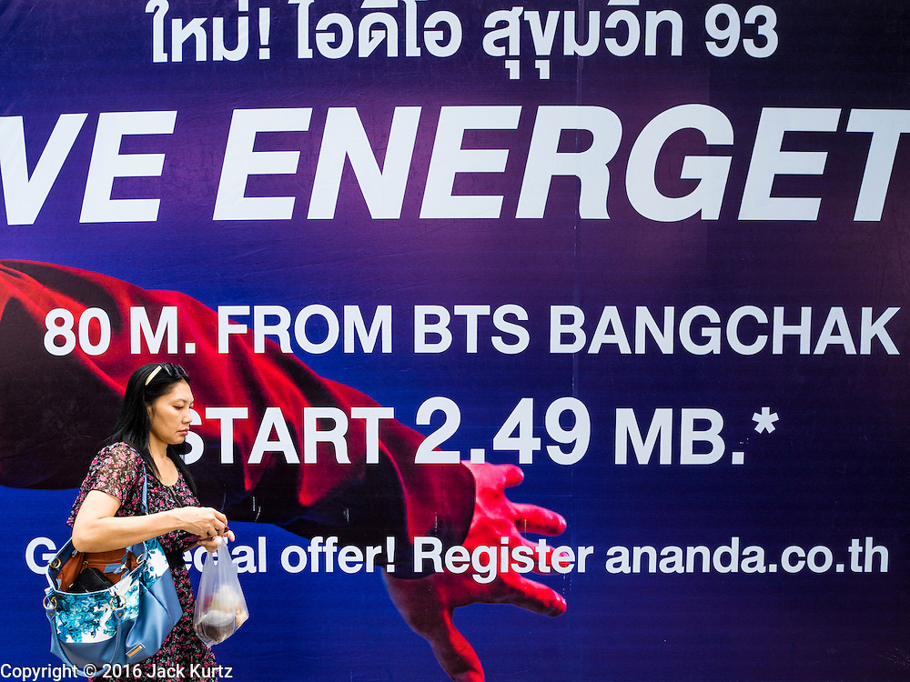 21 SEPTEMBER 2016 - BANGKOK, THAILAND: A pedestrian walks past a sign advertising new condos for sale at the old Bang Chak Market. The condos start at 2.49 million Thai Baht, about $72,000 USD. The market closed permanently on January 4, 2016. The Bang Chak Market served the community around Sois 91-97 on Sukhumvit Road in the Bangkok suburbs. Bangkok city authorities put up notices in late November 2015 that the market would be closed by January 1, 2016 and redevelopment would start shortly after that. Market vendors said condominiums are being built on the land.      PHOTO BY JACK KURTZ