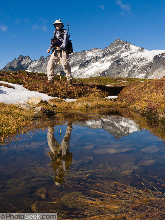 Forbidden Peak and a hiker reflect in a tarn on Sahale Arm in North Cascades National Park, Washington.