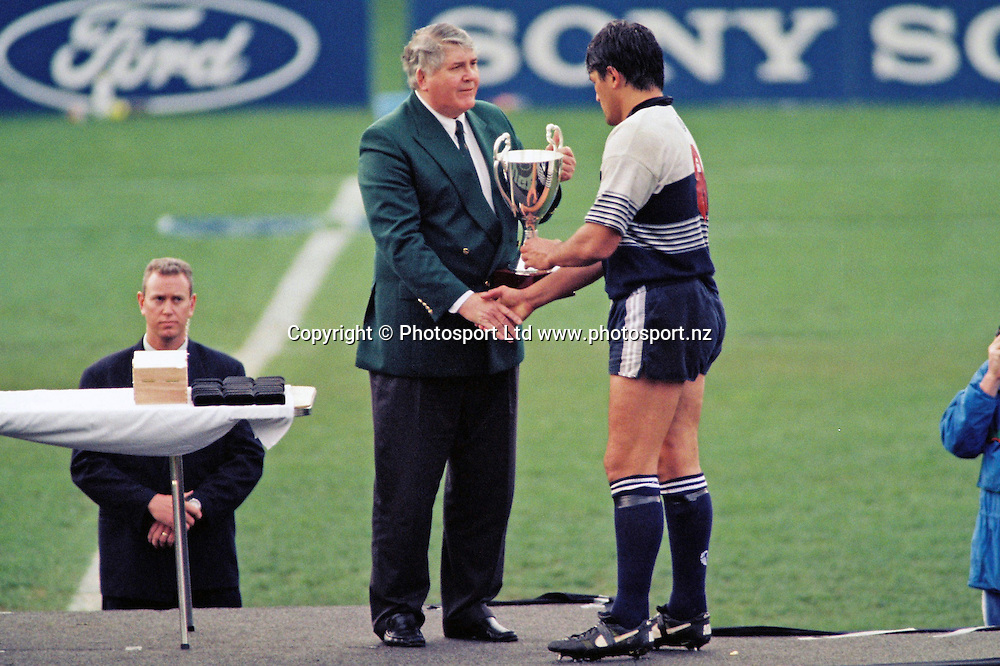 Auckland Blues captain Zinzan Brooke receives the Super 12 trophy from Louis Luyt of South Africa Rugby Union.<br /> Super 12 Rugby final between the Auckland Blues and Natal Sharks at Eden Park, Auckland, New Zealand on 25 May 1996.<br /> The Blues won the final 45-21.<br /> Copyright photo: Andrew Cornaga / www.photosport.nz