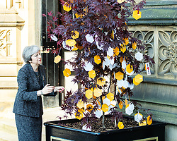 © Licensed to London News Pictures . 22/05/2018 . Manchester , UK . Prime Minister THERESA MAY leaves Manchester Cathedral and hangs a messages on a Tree of Hope outside the Cathedral , after a Service of Remembrance on the first anniversary of the Manchester Arena bombing . On the evening of 22nd May 2017 , Salman Abedi murdered 22 people and seriously injured dozens more , when he exploded a bomb in the  foyer of the Manchester Arena as concert-goers were leaving an Ariana Grande gig . Photo credit : Joel Goodman/LNP