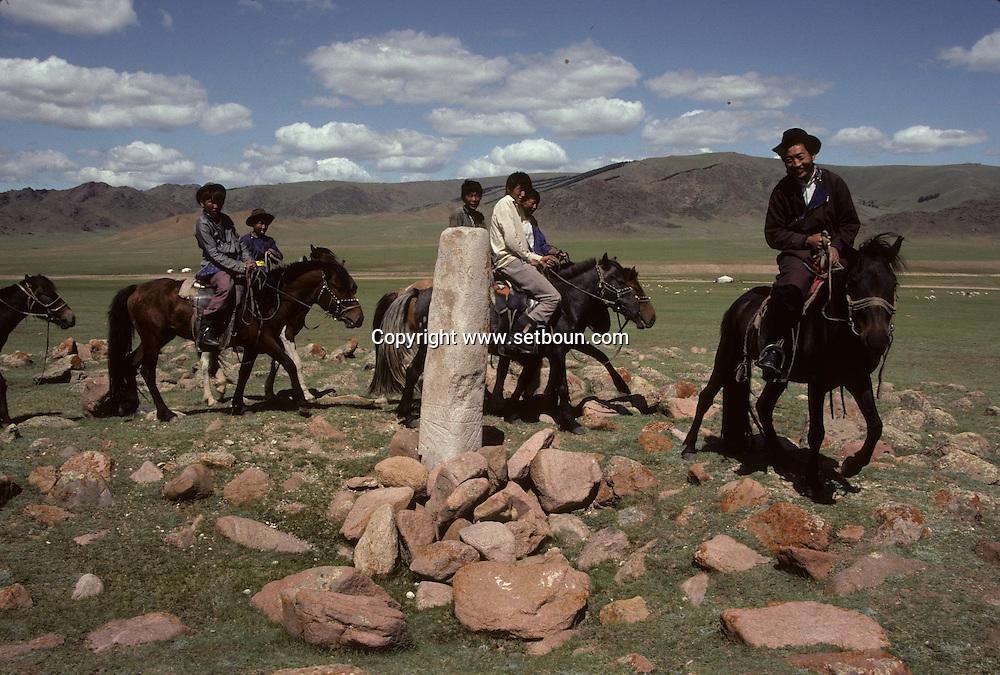 Mongolia. deer stone sculpture; bronze age  Enbulag       / Cavaliers visitant une statue anthropomorphe. (Granit, VI-VIIIème siecle). / Exemple de l'art monumental des nomades d'Asie Centrale, ce type de statue monolithe, représente une  - 'idole de pierre -  (KUN TCHULUU). D'après la coutume du culte des Ancêtres, ce genre de statue était érigée à la surface d'une tombe d'un noble guerrier, à l'époque des Turcs Célestes. Sortes de mémorial, certains de ces monuments ont subi l'érosion du temps et ne subsistent que sous cette forme grossièrement anthropomorphe. (Sum de EKBULAG dans l'aymag de ZAVQAN  / /14    L920720a  /  P0002618
