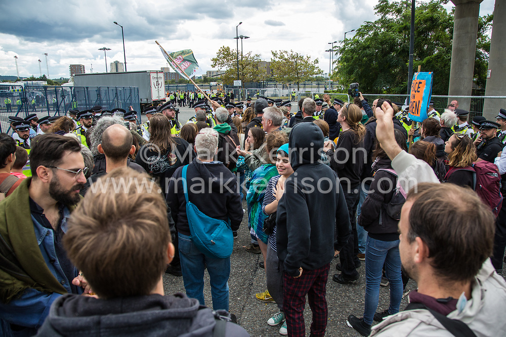 London, UK. 7 September, 2019. Activists wave in the direction of a truck which turned around after the road to ExCel London was blocked on the sixth day of Stop The Arms Fair protests against DSEI, the world's largest arms fair. The sixth day of protests was billed as a Festival of Resistance and included performances, entertainment for children and workshops as well as activities intended to disrupt deliveries to ExCel London for the arms fair.