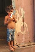A kid slurps on an ice pop in the doorway of his home in el Casco Viejo, Panama City, Panama