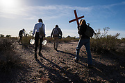 Artist Alvaro Enciso, middle, leads a small group into the desert northwest of Tucson to place handmade crosses where migrants lost their lives and to leave water for migrants making their way north and west.