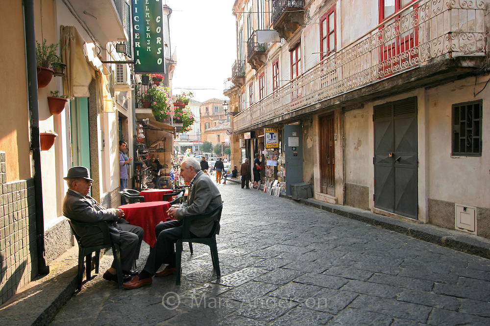 Old men sitting at a cafe table in Pizzo, an Italian village, Calabria, Italy