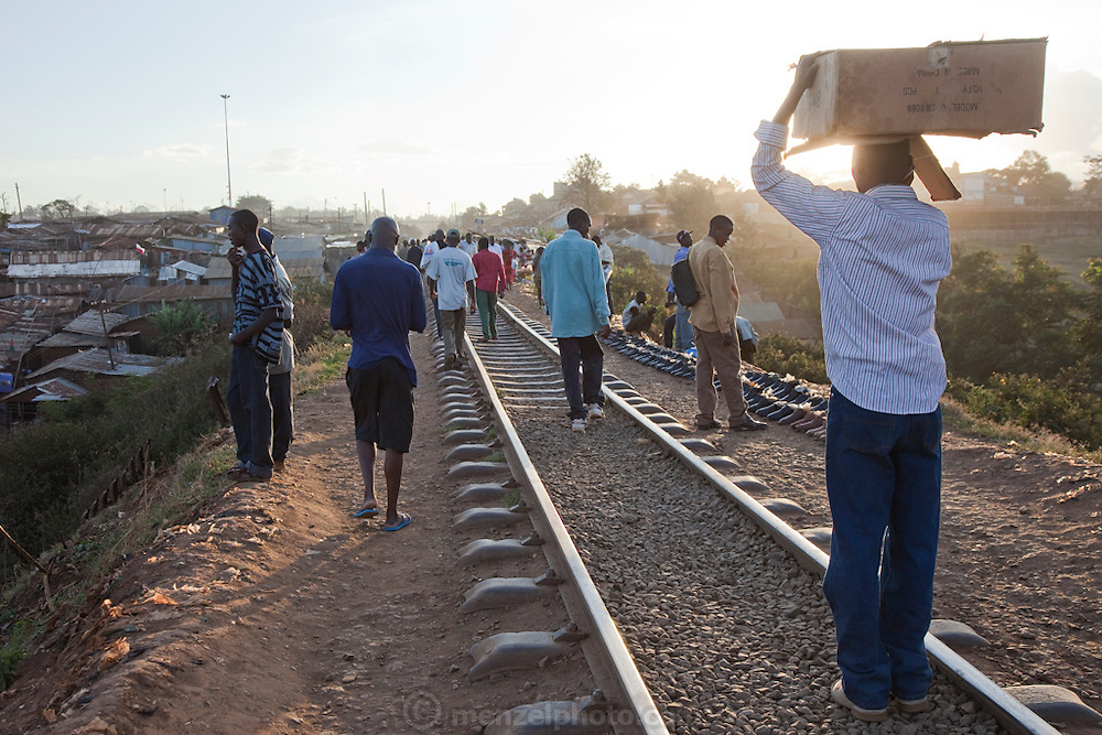 Slum dwellers walk along railway tracks at sunset in the Kibera slum, Nairobi, Kenya. Kibera is Africa's biggest slum with nearly one million inhabitants.