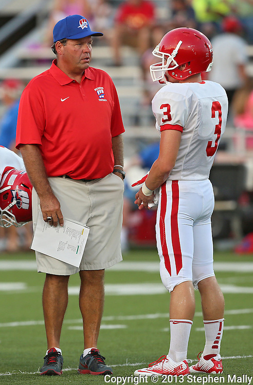 Washington head coach Paul James talks with Reid Snitker (3) during warmups before the start of their game at Kinston Stadium in Cedar Rapids on Friday, August 30, 2013.