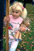 Girl with Miss Piggy doll at Catholic School bike-a-thon age 3.  St Paul Minnesota USA