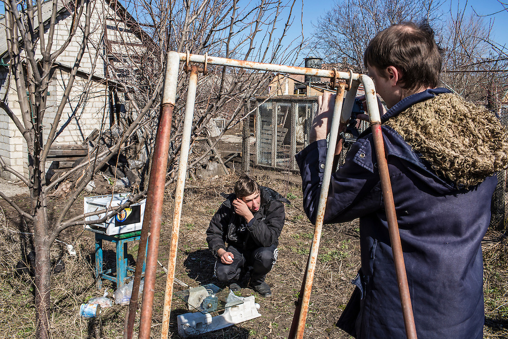 LUHANSK, UKRAINE - MARCH 16, 2015: Pavel Pavlov, left, and Aleksandr Kryukov prepare materials for scientific experiements involving microwaves in the yard of the house where Kryukov lives with his grandmother in Luhansk, Ukraine. The two have created a series of popular YouTube videos involving scientific experiements. CREDIT: Brendan Hoffman for The New York Times