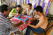 24 APRIL 2014 - CHIANG SAEN, CHIANG RAI, THAILAND: Passengers on a Chinese cargo boat, carrying cars, Red Bull energy drink and passengers to Kunming in China play mahjong. Chinese businesses play an increasingly important role in the Chiang Rai economy. Consumer goods made in China are shipped to Thailand while agricultural products made in Thailand are shipped to China. Large Chinese cargo boats ply the Mekong River as far south as Chiang Saen in the dry season and Chiang Khong when river levels go up in the rainy season.    PHOTO BY JACK KURTZ