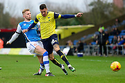 Oxford United striker Marvin Johnson (28) is tackled by Walsall defender (on loan from Southampton) Jason McCarthy (5) during the EFL Sky Bet League 1 match between Oxford United and Walsall at the Kassam Stadium, Oxford, England on 31 December 2016. Photo by Dennis Goodwin.