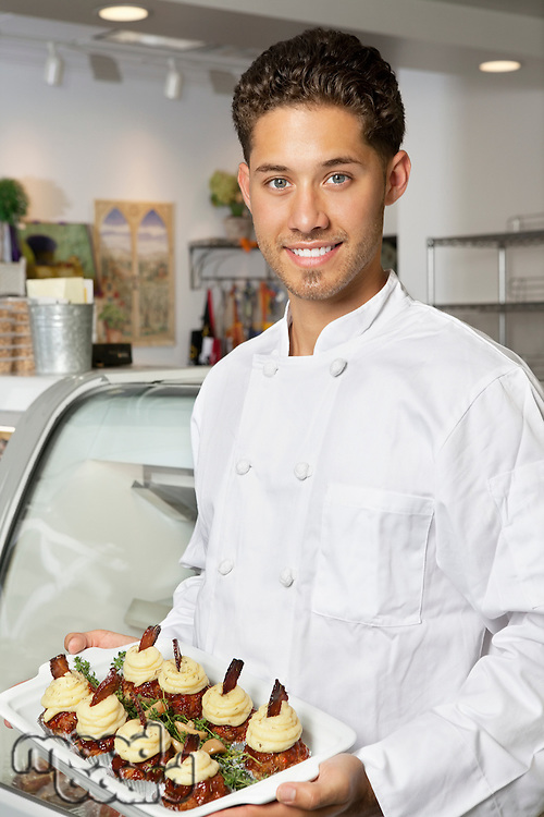 Portrait of young male chef holding dessert in serving dish