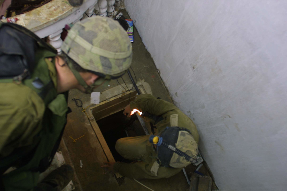 Israeli soldiers with a special forces unit tasked with finding and destroying weapons smuggling tunnels in the Gaza Strip enter a tunnel discovered in a Palestinian home in Rafah on 7 April, 2004. The tunnels exited on the Egyptian side of the border, where Israeli soldiers could not enter.