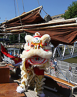 LONDON - JULY 24: Chinatown Olympic Torch Relay runner along with Chinese Dragon and Lion Dancers held a Launch Reception of the Chinatown Ambassador Programme for the London 2012 Olympics on board the Huan Tian Chinese Sailing Boat, River Thames, Tower Bridge, London, UK. July 24, 2012. (Photo by piQtured)