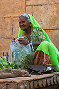 Woman selling vegetables and fruit in Jaisalmer. Rajasthan, INDIA<br /> Founded in 1156 Jaisalmer grew to be a major staging post on the trade route across the forbidding Thar desert from India to the west. It is known as the Golden City as the fort and town's buildings are built from the local yellow sandstone. The bustling narrow streets are lined with tradesmen selling their wares. Many of the smalll shops are occupied by descendents of the original owners. There are many exceptional Havelis (mansions of rich merchants - exquistely carved) both in the fort and the old walled town.
