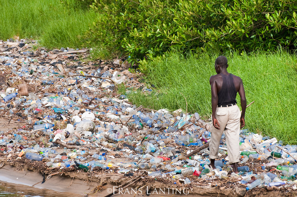 Man on beach polluted with disposable plastic water bottles, Accra, Ghana