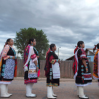 Miss Zuni contestants line up behind the current Miss Zuni Tyra Quetawki to participate in the night parade in Zuni Thursday,