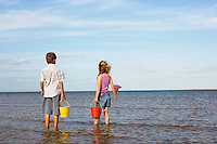 Brother and Sister in surf on beach with buckets and small fishnets looking out at ocean back view