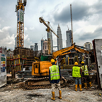 Workers look at the 'Legasi Kampung Baru' project construction work against the backdrop of iconic Petronas Towers in Kampung Baru, Kuala Lumpur, Malaysia, 12 April 2017. Legasi Kampung Baru project consists of 29 storey office tower, 43 storey residential apartments and 48 retail lots and expected to serve as a catalyst for the area's development. The project was built on a land that used to be the focal point of the area for hosting a wedding, meeting, political rallies, sports events called 'Pasar Minggu' since 1960's.