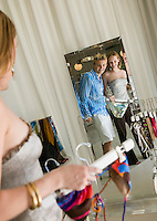 Couple Looking at Clothing in Store Mirror