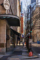 A couple of strollers walk by the 5th Avenue Theatre along its namesake's avenue bearing no traffic in the heart of Downtown Seattle. (March 21, 2020).