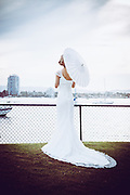 Bride holding and umbrella looking out over the water at seaworld queensland