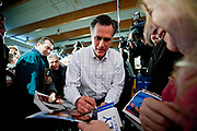 Presidential Hopeful Mitt Romney (R) signs his autograph on pictures and posters at a campaign stop in Salem.