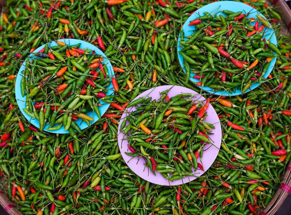 KYAING TONG, MYANMAR - CIRCA DECEMBER 2017: Red and green chili peppers at the Kyaing Tong market.